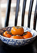 Several persimmons in a bowl on a black chair