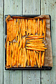Sweet potatoes, peeled and sliced, on a baking tray