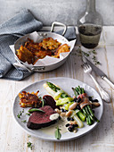 Beef fillet in a milk sauce with potato and pumpkin fritters and vegetables
