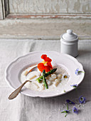 Cream of white asparagus soup with edible flowers