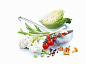 Schöpfkelle mit Tomatenrispe und Frühlingszwiebeln, daneben Wirsing, Blumenkohl, Pfifferlinge, Bohnen und Gewürze
