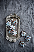 Star-shaped vegan biscuits with pale blue icing and sugar pearls