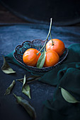 Fresh mandarins with leaves in a wire basket