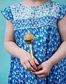 A little girl holding a marble cake pop