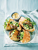 Pitta bread with lamb, cucumber, rocket and feta