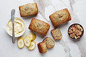 Mini Loaves of banana bread with ingredients on a white marble table