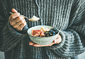 Healthy winter breakfast: Woman in woolen sweater eating rice coconut porridge with figs, berries, hazelnuts