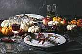 Autumn holiday table decoration setting with decorative pumpkins, apples, red leaves, empty plate with vintage cutlery