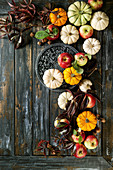 Autumn holiday table decoration setting with decorative pumpkins, apples, red leaves over wooden table
