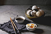 Bowl with different size rice balls with black sesame and seaweed nori, served with soft boiled eggs, soy sauce