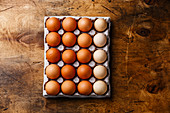 Fresh brown and speckled chicken Eggs in eco cardboard paper tray container on wooden background