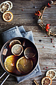 Hot winter drink. Mulled wine with orange, lemon and spices in a casserole on wooden rustic table