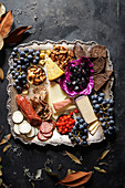Square metal tray of fall charceuterie with delicate foliage around tray on dark rustic background