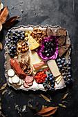 Verschiedene Häppchen und Früchte auf quadratischer Servierplatte