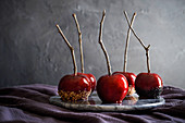 Marble tray of beautiful, red, candy apples on dark purple linen