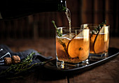 Whiskey cocktail with fresh thyme and pear on a rustic wood background