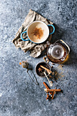 Vintage blue pot of traditional indian masala chai tea with ingredients above
