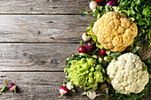 Variety of fresh raw organic colorful cauliflower, cabbage romanesco and radish with bundle of coriander