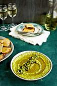 Roasted Poblano Cilantro Pesto in a ceramic bowl, served with sourdough bread