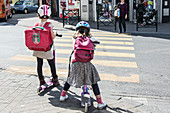Girls on scooters at a road crossing