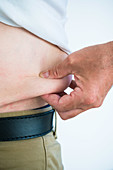 Man squeezing fat at waist