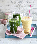 Green spinach and apricot smoothie, and a mango drink yoghurt