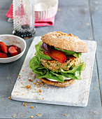 Vegetarian quinoa burger with avocado and plums