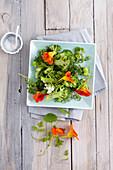 Warm broccoli salad with fresh wild herbs and edible flowers