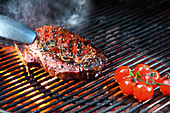 Beef steak and tomatoes on a barbecue