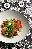 Tagliata with potatoes, parmesan cheese, pepper, salt, rocket and tomatoes