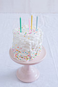 Cake with sprinkles decoration on a pink stand
