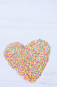 A heart shape made with colorful sprinkles on a white surface
