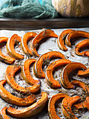 Baked pumpkin slices on baking parchment with rosemary