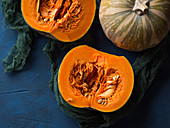 Raw small pumpkin cut in two parts on blue background