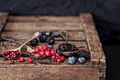 Rote Johannisbeeren, Granatapfelkerne, Blaubeeren und Brombeeren auf Holzkiste