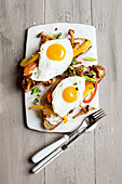 Grilled bread topped with vegetables and fried eggs for vegetarians