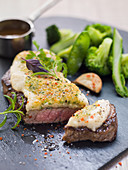 Roast beef with gratin celery puree on green vegetables