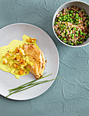 Chicken breast fillets with peas, bulgur wheat, and apricot curry sauce