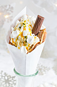 A bubble waffle with frozen yoghurt, pistachios, meringue, chocolate flake and mango sauce (Christmas)