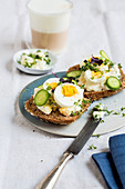 Wholemeal roll topped with herb cream cheese and hard-boiled egg