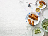 Fish fingers with a cornflake coating served with Joppie sauce and cucumber salad