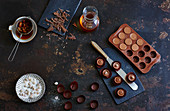 Pralines in moulds, rum-soaked raisins and chopped cooking chocolate