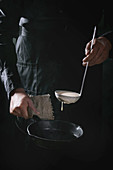 Man chef in black apron pouring dough from ladle for cooking pancakes in cast-iron pan