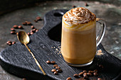 Glass of spicy pumpkin latte with whipped cream and cinnamon standing on black serving board