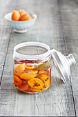 A jar of preserved apricots with peppercorns