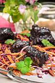 Short ribs with a blueberry glaze and shredded carrot and red cabbage