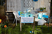 Table set in shades of blue with handmade decorations in spring garden