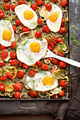 Grilled tomatoes with fennel and fried eggs on a baking tray
