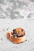 Yeast bun filled with chocolate and chopped hazelnuts, topped with icing and candied orange peel