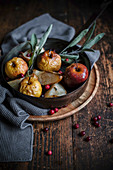 Baked apples and baked pears with cranberries and sage